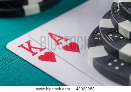 Poker. King and Ace with few chips on the poker table.