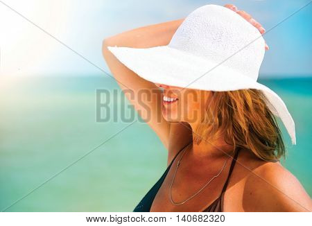 Beautiful middle aged woman in a big white hat tanning on the beach. Beauty female portrait over blu