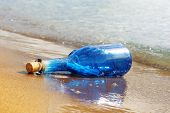 Blue glass bottle on yellow beach's sand