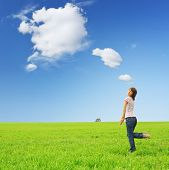 Playfull young woman on green grass with fairy clouds