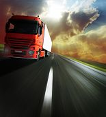 Heavy truck on blurry asphalt road under sunlight