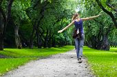 stock photo of long distance  - Woman walking on path in green summer park - JPG