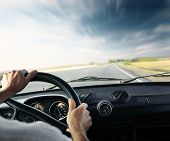 Driver's hands on a steering wheel of a car and blue sky with blurred clouds