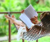 stock photo of reading book  - Young woman reading a book lying in hammock - JPG