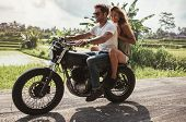 Young Couple Enjoying Motorcycle Ride On Country Road poster