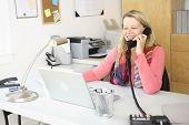 Frau im Büro zu Hause am Telefon