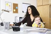 Woman working in home office with baby