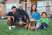 Family with dog in grass by home