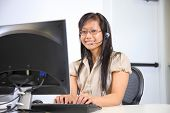 picture of asian woman  - Asian woman with headset working at computer - JPG