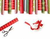 Rolls of colored wrapping  paper with scissors and gift on white background