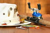 Fishing reel with hat and color lures on wood
