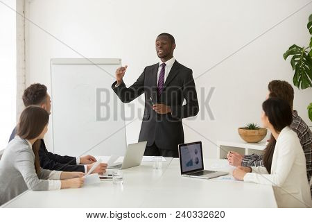 poster of Confident African Speaker Business Coach In Suit Giving Presentation Training Sales Team In Office,