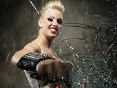 stock photo of brass knuckles  - Punk girl breaking glass with a brass knuckles - JPG