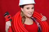 Female construction worker holding corrugated tubing and a pipe wrench