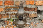 An Old Kerosene Lamp. Old Lamp. Kerosene Lamp. Kerosene Lamp On A Background Of Red Bricks. poster