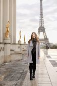 Young Female Person In Grey Coat Standing On Trocadero Square Near Gilded Statues And Eiffel Tower I poster