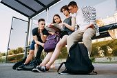 Traveling, Sightseeing, Group Travel, City Tour, Togetherness. Tourists Sitting At Bus Stop Planning poster