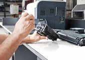 stock photo of cartridge  - hands repairing laser toner Cartridge on white table - JPG