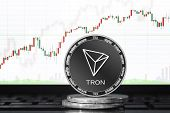 Tron (trx) Cryptocurrency; Physical Concept Tron (tronix) Coin On The Background Of The Chart poster