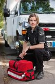 Confident EMS paramedic kneeling by portable oxygen unit and ambulance
