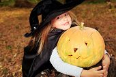 Shot of a little girl in halloween costume posing with pumpkin outdoor.