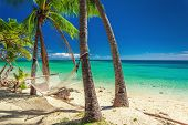 Empty hammock in the shade of palm trees on vibrant tropical Fiji Islands poster