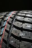 Brand new winter tire pattern on black background poster