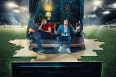 Ardent Fans Sitting On The Sofa And Watching Tv In The Middle Of A Football Field. Soccer Football C poster