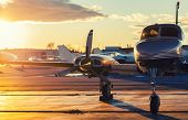 Small Aviation: Private Jet Is Parked On A Tarmac In A Beautiful Sunset Light poster