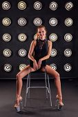 Fashion Shoot Of A Sexy Striptease Dancer On A Chair In Studio. poster