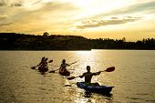 Friends Paddling Kayaks on the Beautiful River or Lake under the Dramatic Evening Sky at Sunset poster