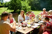 leisure, holidays and people concept - happy family having festive dinner or summer garden party poster