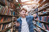 Handsome Young Man Stands In A Library With A Smearphone In His Hand And Shows His Finger Down. The  poster