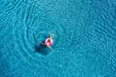 Aerial View Of Young Woman Swimming In The Sea With Transparent Water poster