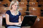 Joven estudiante utilizando la computadora portátil en el hall de la Universidad
