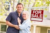 Caucasian Couple in Front of For Sale Real Estate Sign and House poster