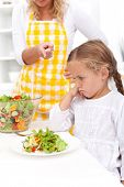 Mother training a healthy eating habit in her child - eating vegetable salad