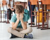Little boy crying on floor in classroom. Bullying in school poster