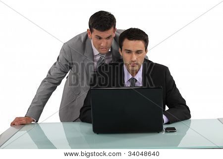 Постер, плакат: Бизнесмены глядя на ноутбук, холст на подрамнике