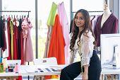 Portrait of young adult fashion designer as owner entrepreneur at her atelier studio. Using for entr poster