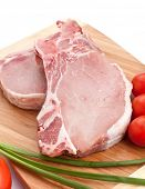 two raw pork chops with vegetables on
