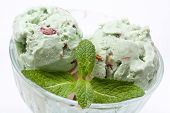 scoops of  ice cream with mint leaves in a glass