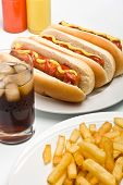 glass of cola, french fries and three classic hot dogs with mustard and ketchup on a plate