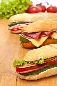 group of long baguette sandwiches with lettuce, vegetables, salami, ham and cheese on a wooden table