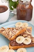 chocolate and peanut buttered toasts with pieces of bananas on a plate, an open chocolate spread co
