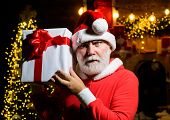 Santa With Box. Bearded Man In Santa Claus Costume. Serious Santa Claus Holds Present Box. Christmas poster