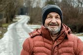 Happy smiling elderly bearded man face, winter portrait outdoors in a Russian village near the road poster
