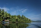 Traditional Boat And Jungle Hut On The Tatai River In The Cardamom Mountains Of Cambodia poster