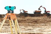 foto of theodolite  - Surveying measuring equipment level theodolite on tripod at construction building area site - JPG