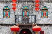 Detail of Chinese old style building facade with colorful windows and hanging lanterns as an ornament.This is architectural style in the begin of last century's.